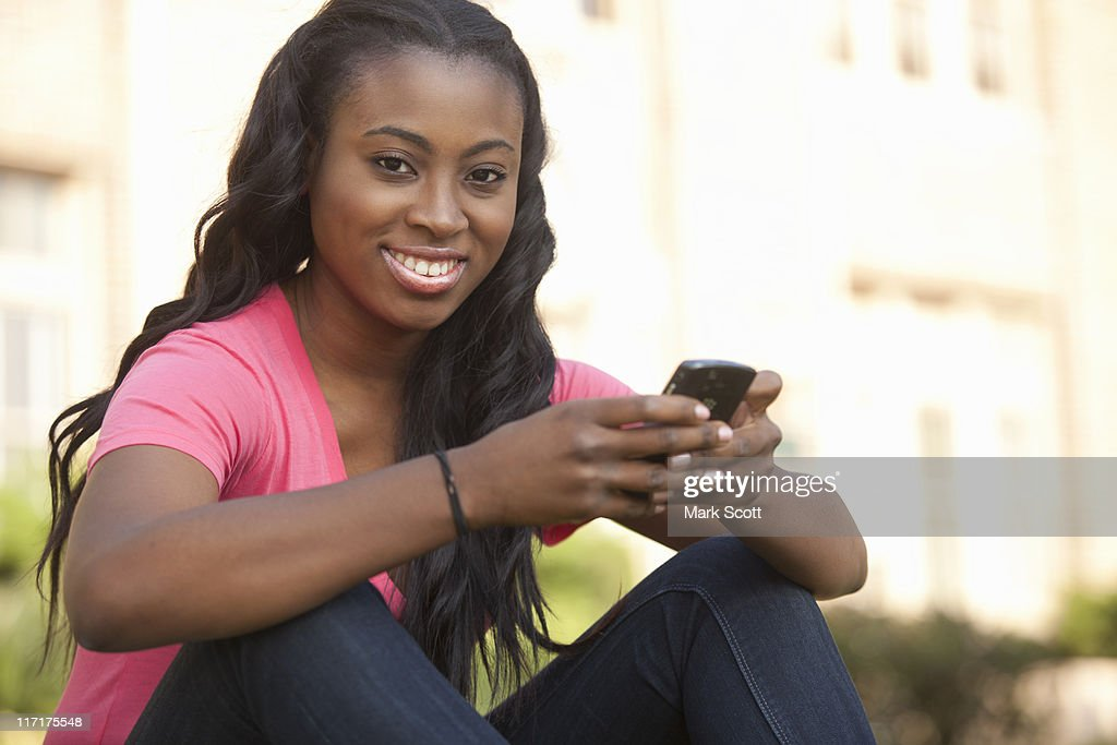 African American woman texting outside : Stock Photo