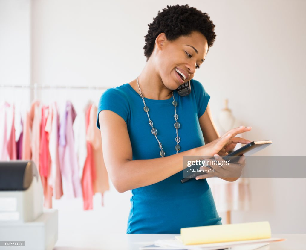 African American woman using a digital tablet at work : Stock Photo