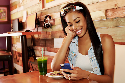 African American woman using cell phone in cafe