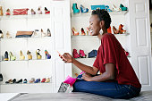 African American woman using cell phone in shoe store