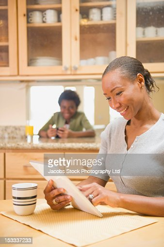African American woman using digital tablet in kitchen : Stock Photo
