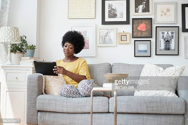 African American woman using digital tablet on sofa