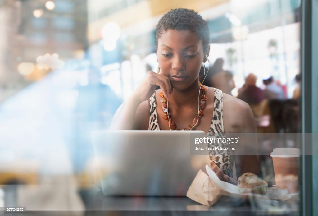 African American woman using laptop in cafe : Stock Photo