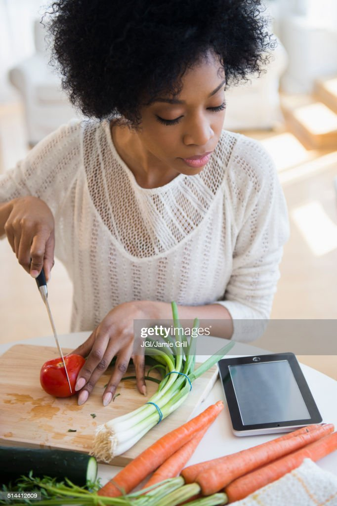 African American woman using tablet computer to cook