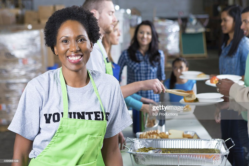 African American woman volunteering at community soup kitchen : Stock Photo