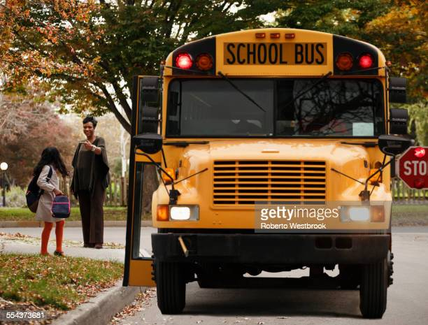 African American woman waiting with daughter for school bus