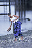 African American Woman Walking Barefoot On A Rocky Beach