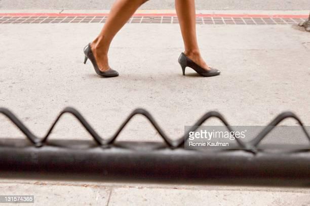 African American woman walking in high heels on sidewalk