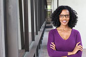A pretty African american woman wearing glasses at work.