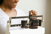 African American woman weighing herself on scale