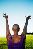 African American woman with arms outstretched in park
