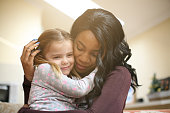 African American woman playing with girl. Woman hugging her adopted daughter.'n