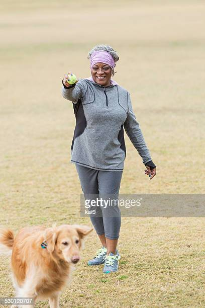 African American woman with golden retriever playing fetch