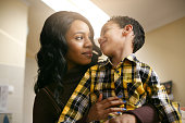 African American woman with her son. African American woman spending time with her son at home. Looking each other.