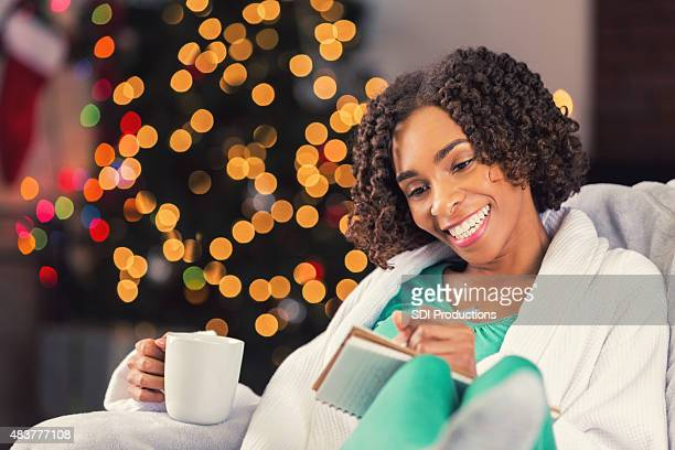 African American woman writing in journal on Christmas morning