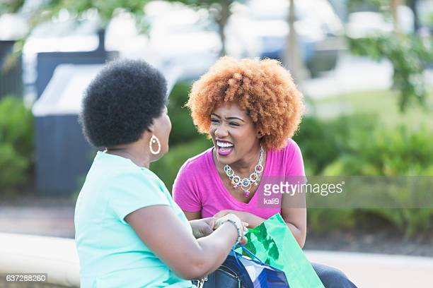 African American women with shopping bags, laughing