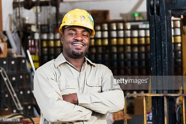 African American worker in print shop, next to forklift