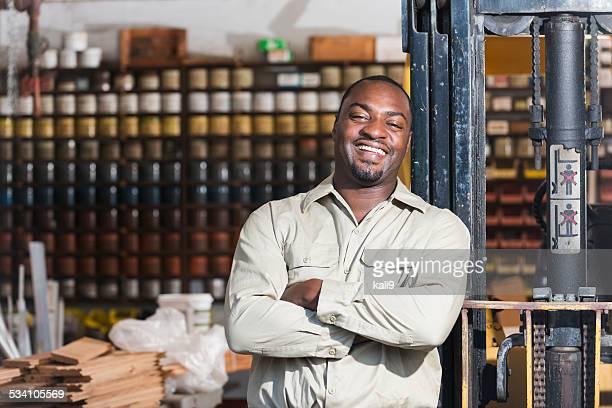Afro-americano trabalho em loja de impressão, junto de máquina elevadora de cargas
