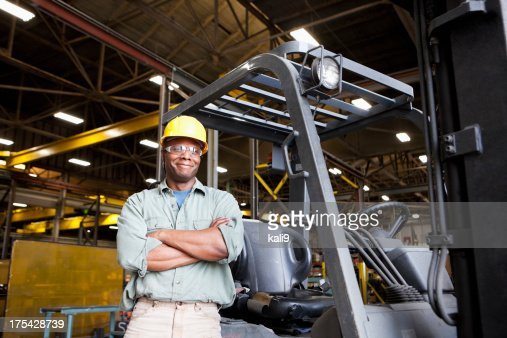 African American worker standing beside forklift