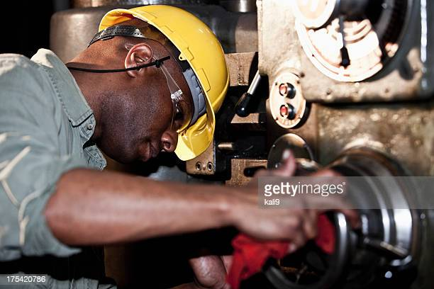 African American worker using drill press