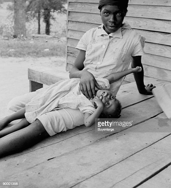 African American young girl with a small child on a porch