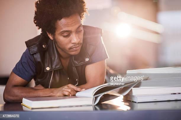Afro-americano jovem ler um livro e estudar.