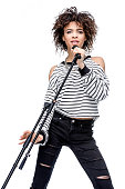 african american young woman singing with microphone isolated on white, female singer with microphone concept