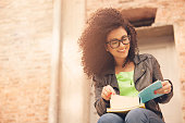 African american young woman smiling with books and glasses outdoors