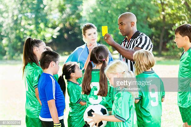 African American youth soccer referee explains penalty to teams