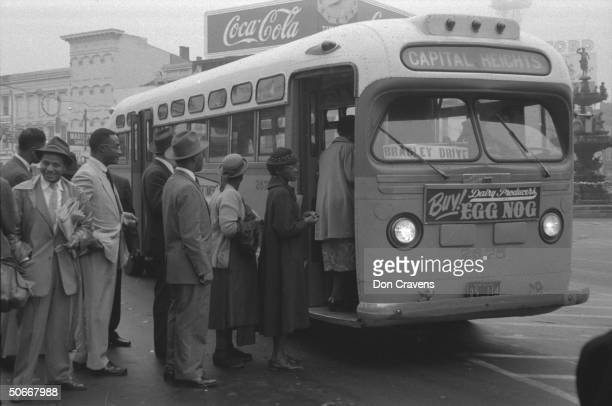 African Americans boarding an integrated bus through the onceforbidden front door following Supreme Court ruling ending successful 381 day boycott of...