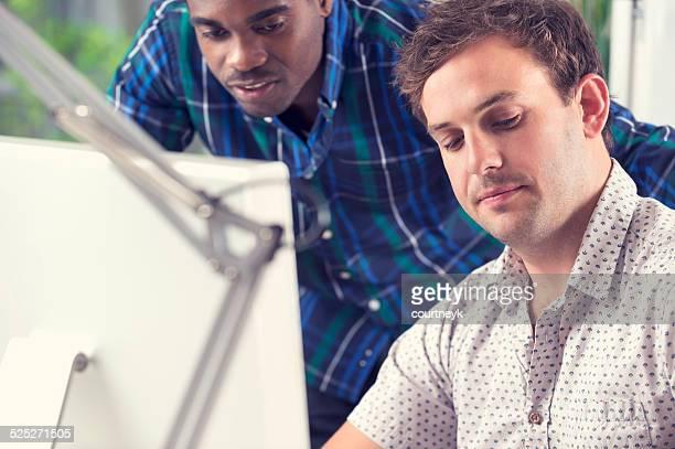 Afrikanischer und kaukasischen Männer arbeiten zusammen Blick auf computer.