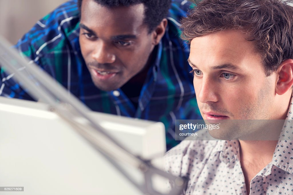African and Caucasian men working together looking at computer.