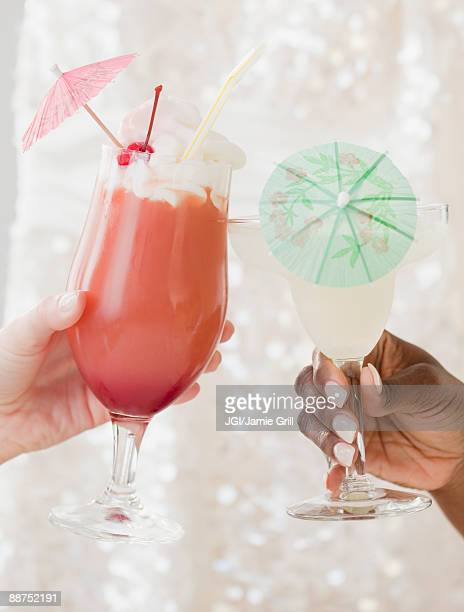 African and Caucasian woman drinking frozen cocktails