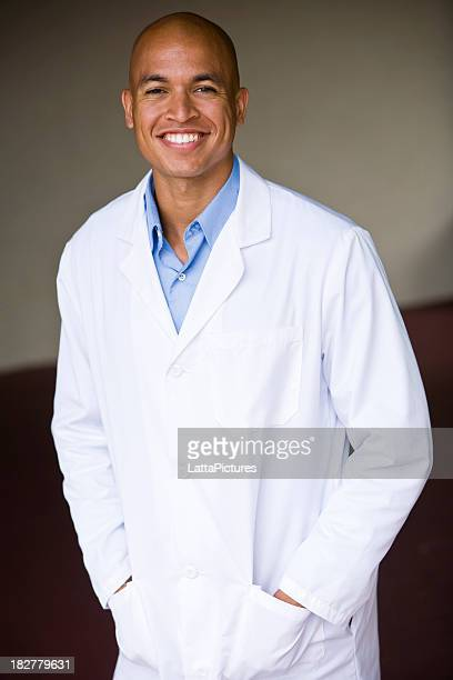 African Asian man wearing lab coat with hands in pockets