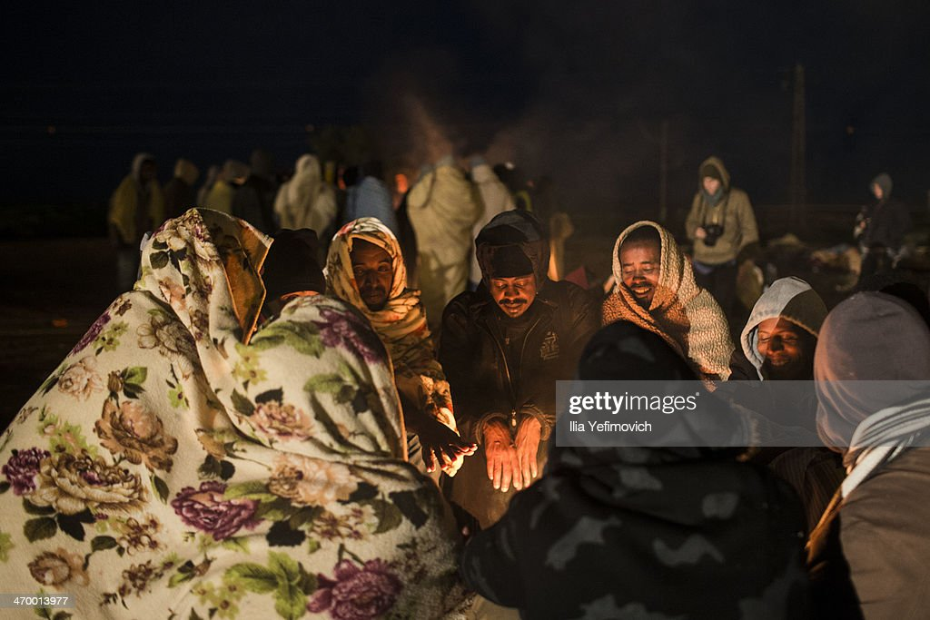 African asylum seekers gather around the fire in the early morning of a second day of protest outside the Holot detention centre where hundreds of migrants are being held February 18, 2014 in the southern Negev desert of Israel. More than 50,000 illegal African migrants are seeking asylum after escaping war and government repression in their native lands.