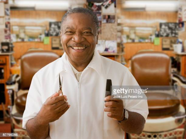 African barber holding comb and scissors in barbershop