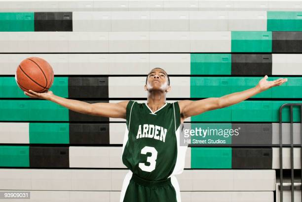 African basketball player holding ball with arms outstretched