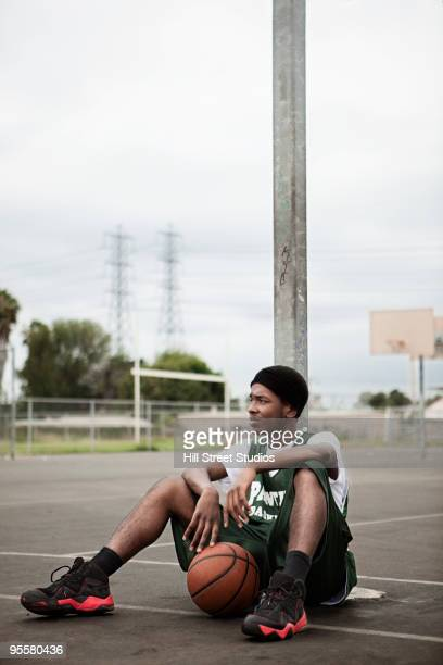 African basketball player sitting with ball under basket