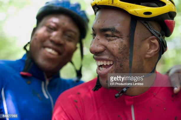 African bicyclists with mud on their faces