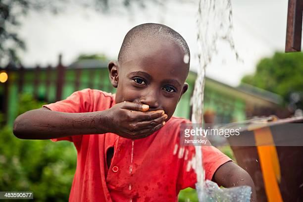Ragazzo africano con pompa dell'acqua