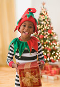 African boy dressed as elf holding Christmas gift