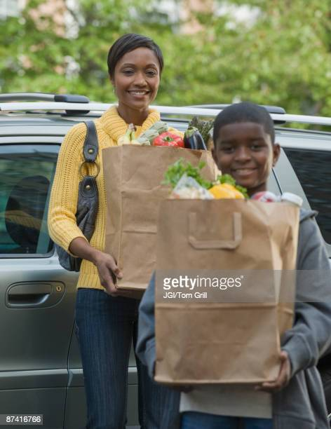 African boy helping mother unload groceries
