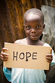 African Boy Holding A Sign With Hope Written On It