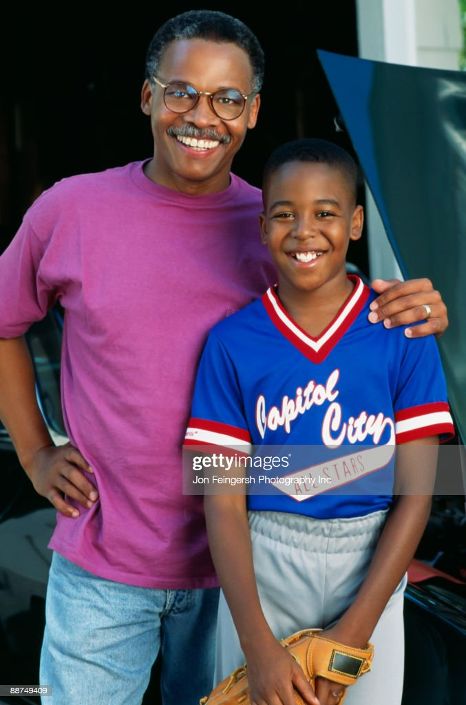 African boy in baseball uniform with father : Stock Photo