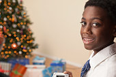 African boy in braces near Christmas tree