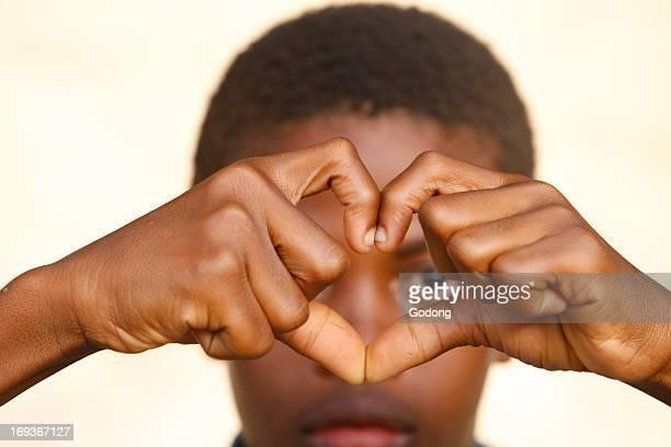 African boy making a heart shape Togo