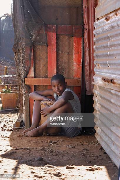 Garçon africain en dehors de son shack