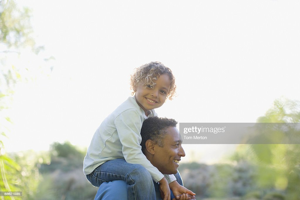 African boy sitting on fathers shoulders : Stock Photo
