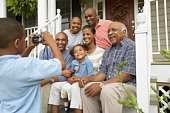 African boy taking photograph of multi-generational family smiling on porch