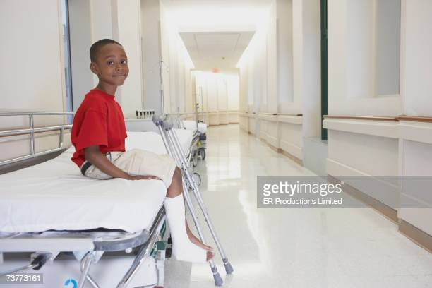 African boy with broken leg and crutches sitting on bed in hospital corridor